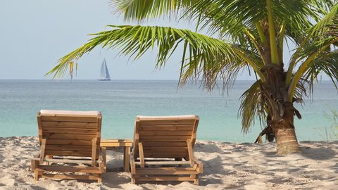 Wooden lounge sun beds under coconut palm tree on exotic beach and boat sailing away on sea