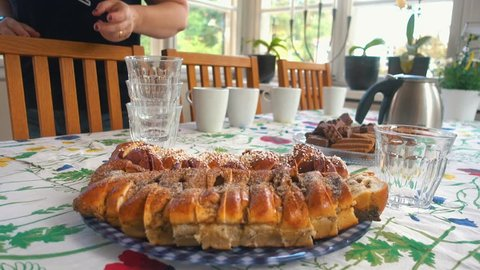women is cleaning and brining out cinnamonbuns and coffe for a swedish midsummer fika or afternoon tea