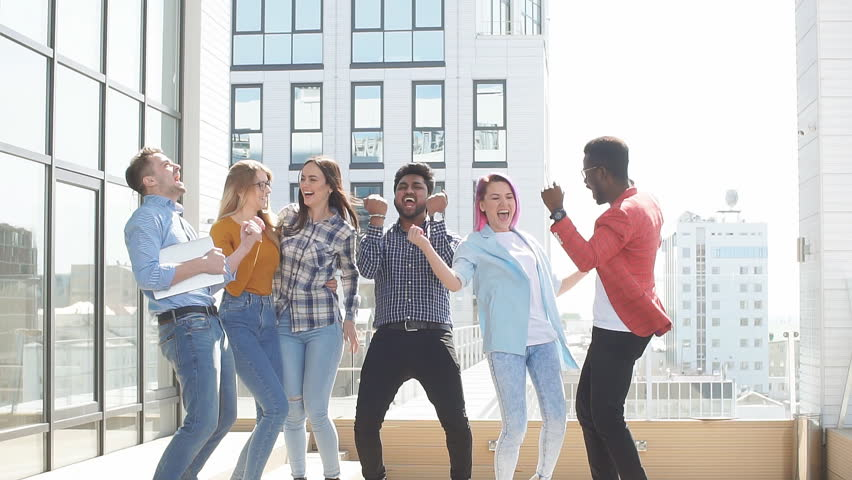 Multiracial heterosexual group of students having fun on roof party dancing and listening music at daytime on the roof area against glass office buildings background | Shutterstock HD Video #1013800013