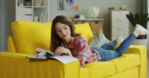 Pretty Caucasian young woman lying on the yellow couch, flipping pages and reading fashion magazine at home.