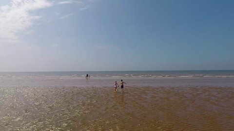 An aerial view of two children running into the sea at Blackpool beach in the UK