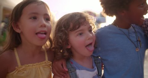 Young multi-ethnic kids having fun being silly with their tongues out at amusement park