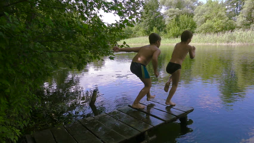 Two boys jump together from pier to the river in the forest, slow motion | Shutterstock HD Video #1013821433