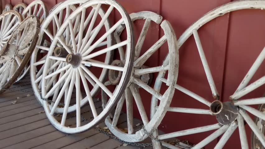 Several old Wooden Wagon wheels all lined up along a wall