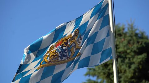 4K slow motion footage of bavarian flag waving in the wind with tree in the background