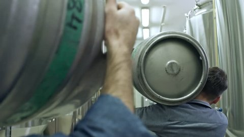 Rear view of two male brewery workers walking through rows of vessels in modern brewhouse and carrying kegs with beer