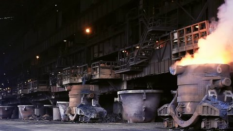 Slow pan of a steel mill blast furnace with smoking crucible filled with molten metal