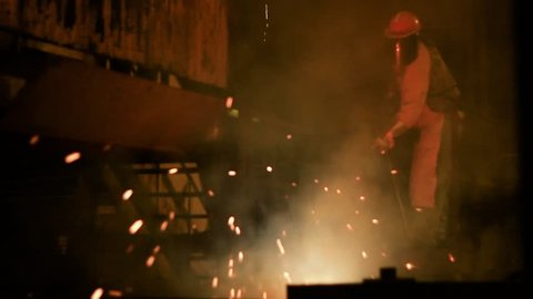 Steelworks Employee using an Oxygen Lance to create sparks while where protective PPE Clothing