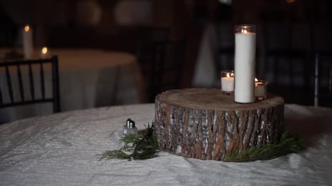 Decorative candles being used as the centerpiece of a table at a wedding reception.