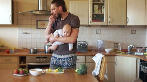 A young modern father cooks food in the kitchen, holding a three-month-old baby in his arms. Single parent, father's day. A man has a stylish beard and a ponytail on the back of his head