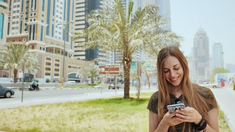 The girl dials a number or message on the smartphone against the backdrop of the city streets of Dubai.