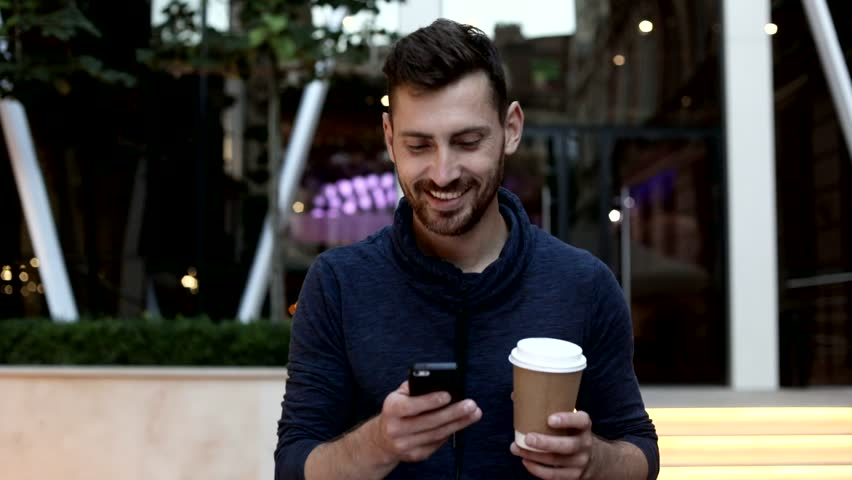 Handsome Young Man Walking in the Street near the Huge Glass Building. Typing a Message on his Mobile Phone. Smiling, Enjoying the Evening. Holding a Paper Cup with Black Coffee. | Shutterstock HD Video #1013876873