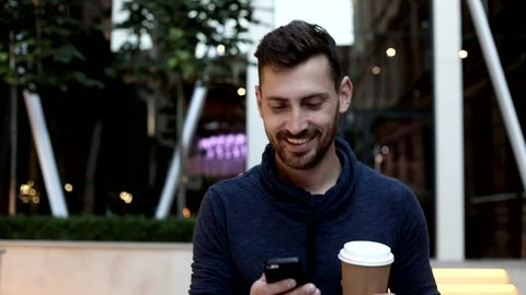Handsome Young Man Walking in the Street near the Huge Glass Building. Typing a Message on his Mobile Phone. Smiling, Enjoying the Evening. Holding a Paper Cup with Black Coffee.
