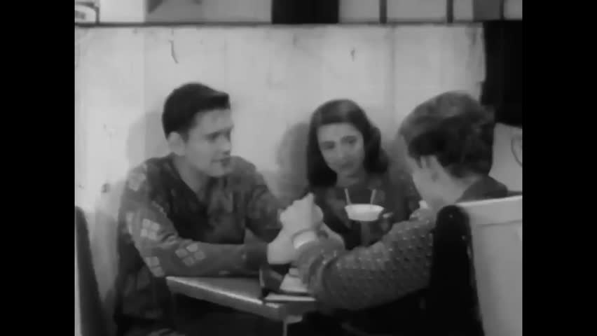 CIRCA 1940s - A shy boy makes eye contact with a girl he'd like to take to a school dance in 1947.