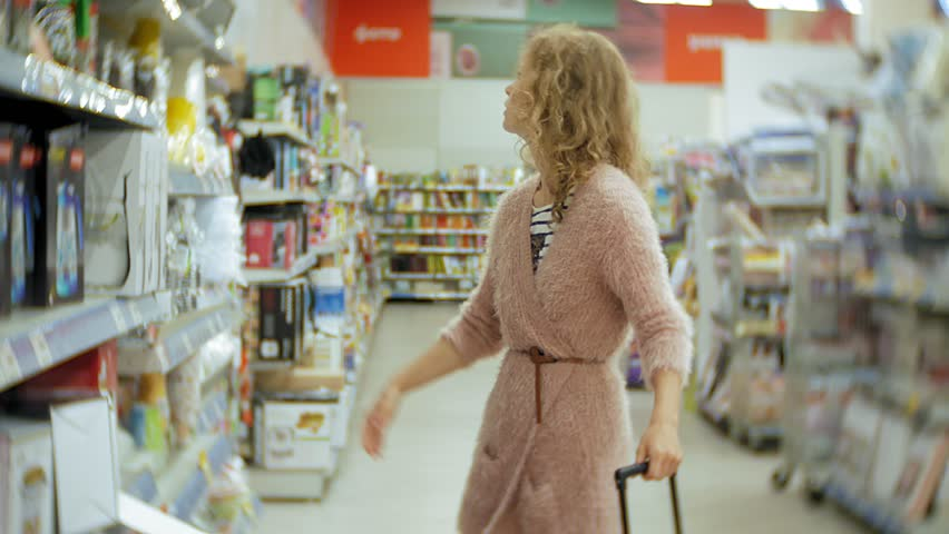 Young woman stands near the supermarket shelf and selects the products 4k | Shutterstock HD Video #1013883863