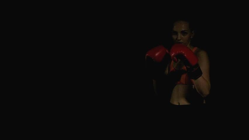 Woman muay thai. Real muay thai woman doing elbow move. Black background. White female. Slow motion.