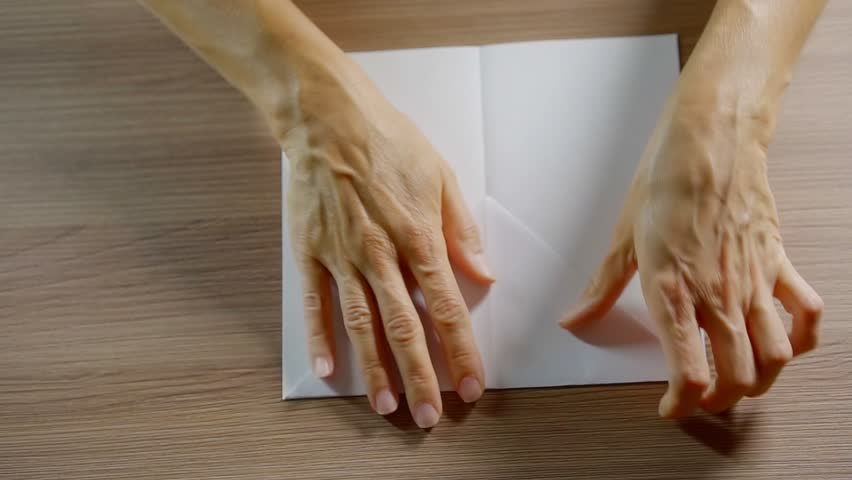 Shot from above of a woman's hands folding a piece of paper.