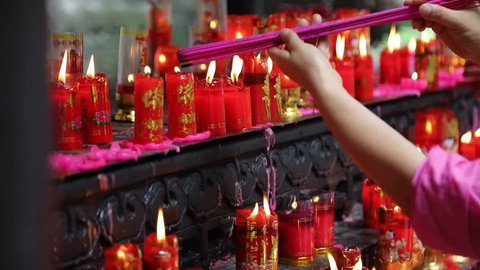 Chinese people burning incenses and praying.