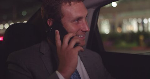 Young business man talking on phone in back seat of car while driving around busy city at night