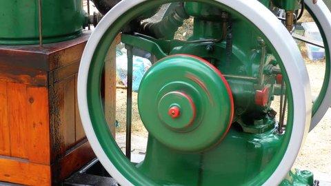 Flywheel turning on a stationary engine machine pump