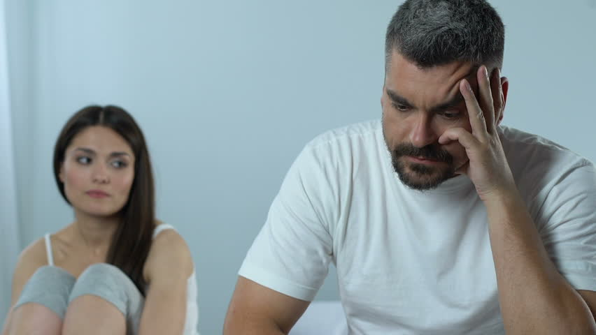 Upset man and supportive wife sitting in bedroom, impotence, family crisis
