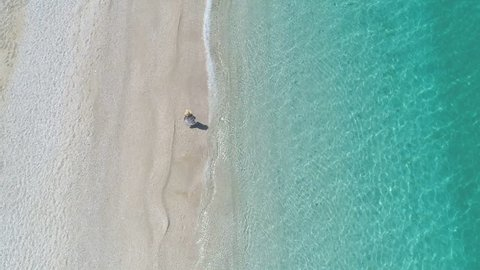 Aerial - Top view of woman in a dress walking on paradise beach