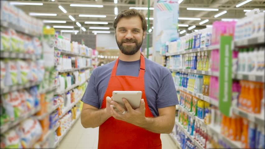 Handsome smiling supermarket employee with beard using digital tablet standing among shelves In supermarket | Shutterstock HD Video #1013929313