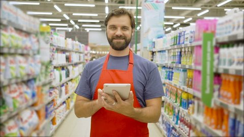 Handsome smiling supermarket employee with beard using digital tablet standing among shelves In supermarket
