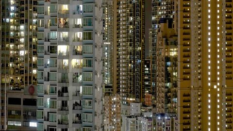 Hong Kong dense apartment buildings timelapse. Chinese crowded city with lights turning on and off at midnight. Fast paced modern Asian night-scape time lapse in urban metropolis.