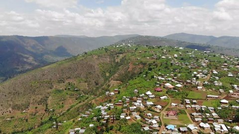 Aerial drone footage of a village in Rwanda. Gorgeous green hills and mountains, rural village with red roofs and brown clay streets. Rwanda is one of the most beautiful countries in Africa.