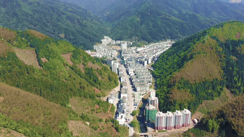 Drone aerial shot of mountain valley city Huangshan city in Tunxi, Anhui. Huangshan mountain tourist attraction, with quaint modern village between giant mountains during very hot summer in China.