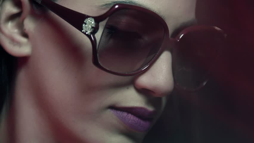 Moving shot from the Mediterranean looking young woman's neckline with jewellery to her face wearing makeup and sunglasses as she looks to camera.