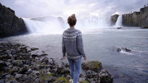 Young woman contemplating the magnificent waterfall and wandering in Iceland, Godafoss falls. People travel exploration concept. Tourism tourist girl travel world northern countries slow motion