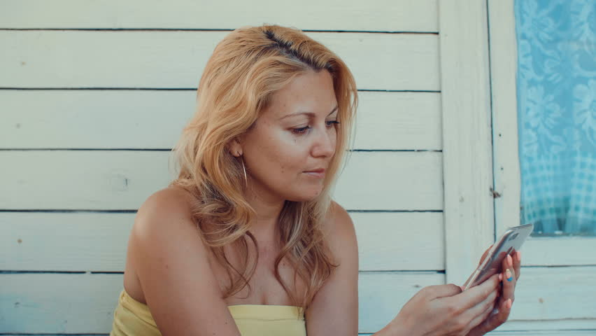 Blonde woman typing message by mobile phone and resting on summer terrace | Shutterstock HD Video #1013951993