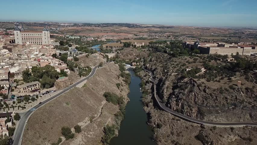 Aerial view of an ancient Spanish city Toledo in Castilla la Mancha. Drone flying over the river Tajo with the historic center and Alcazar to the left and the militar Academy to the right