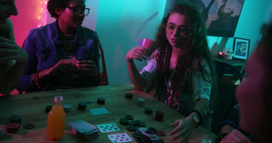 Young woman winning chips at poker card game while hanging out with friends at home