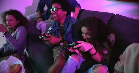 Happy multi-ethnic teenage friends relaxing on living room sofa and playing video games