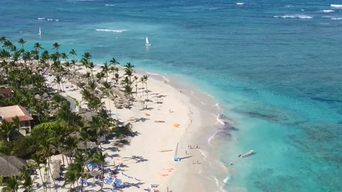 Dominican Republic Punta Cana beach, exotic palm trees, white sand, white sand / Top view of the island. A beach with white sand and blue sea. Beautiful palm trees, beautiful coast.
