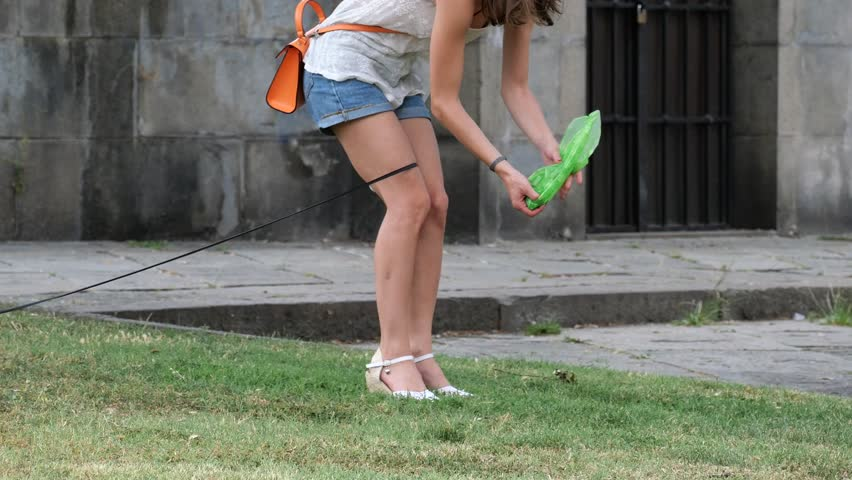 city of Genoa, Italy -  a girl collects her dog's poop
