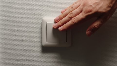 Light is Off - Male hand switch off a button on a light-grey wall, front view