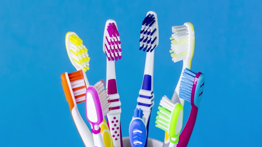 Colorful toothbrushes in spinning toothbrush cup on blue background, close-up and seamless loop.