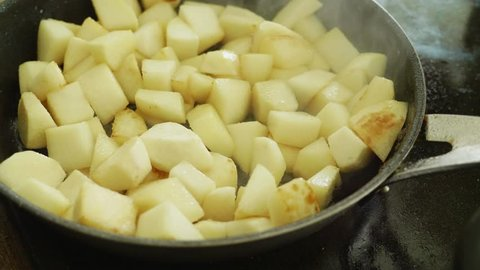White turnip pieces being fried in a pan