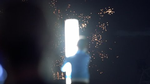 Silhouette of unrecognizable boy on pillar during fireworks explosions during national Holiday Bastille Day on July 1 in Paris, France