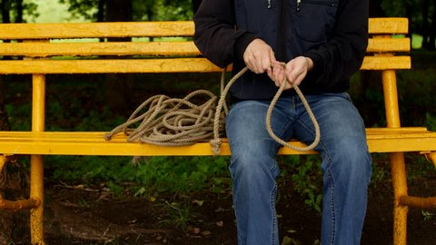 A man sits on a bench and makes a loop from the rope, prepares for suicide, preparation for suicide, hang oneself