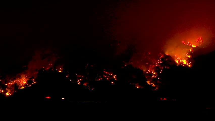 2017 - the Thomas Fire burns in the hills above the 101 freeway near Ventura and Santa Barbara, California.   Shutterstock HD Video #1014058793