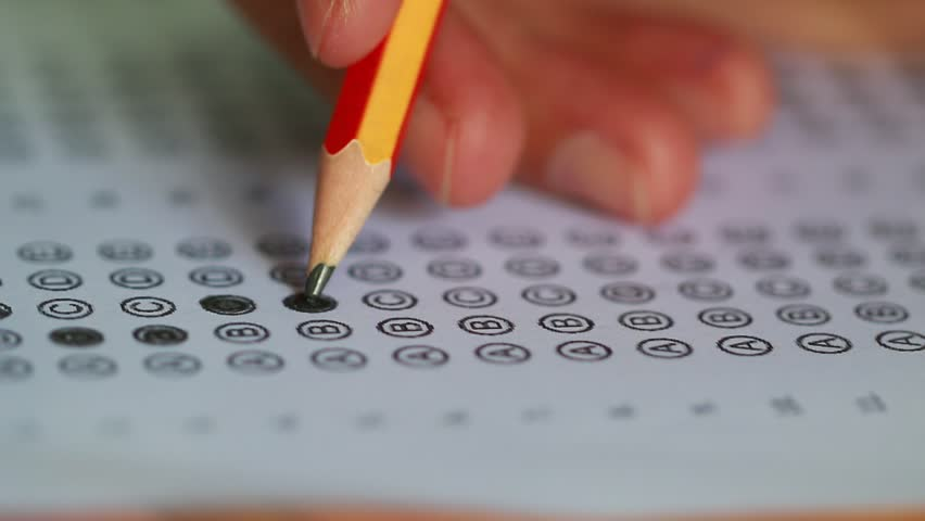 Student taking exams, writing examination on paper answer sheet optical form of standardized test on desk doing final exam in classroom, Examination sitting on row chair in school. | Shutterstock HD Video #1014078953