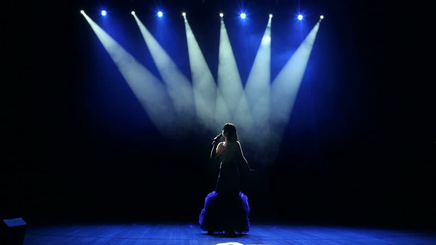 A young woman in a luxurious evening dress sings a song and dances on a dark smoky stage.