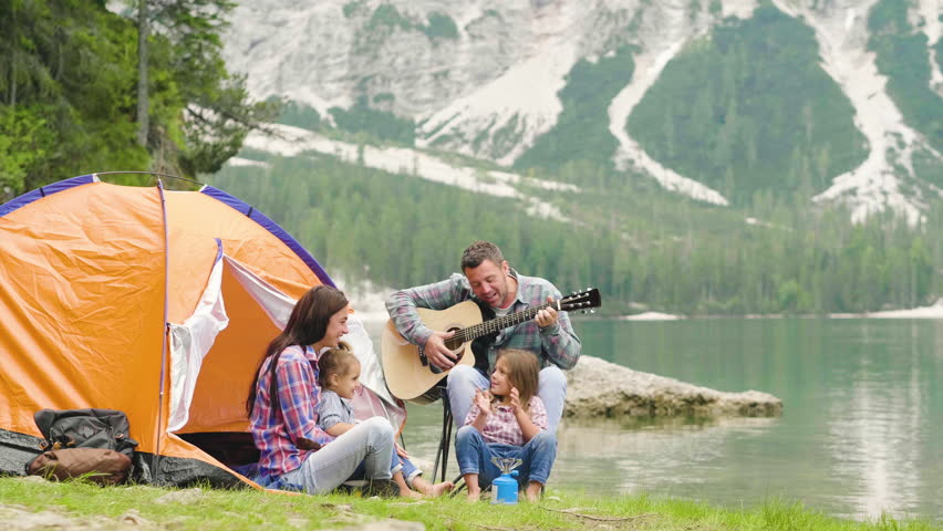 A happy family camping at the lake, playing the guitar and singing a song together in front of the tent. Concept of: trekking, nature, family.