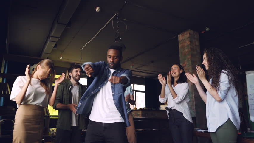 Slow motion of happy office worker African American guy dancing at corporate party while his team members are clapping hands, looking at him and laughing. | Shutterstock HD Video #1014103493