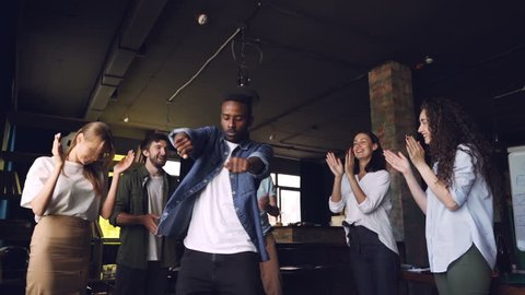 Slow motion of happy office worker African American guy dancing at corporate party while his team members are clapping hands, looking at him and laughing.